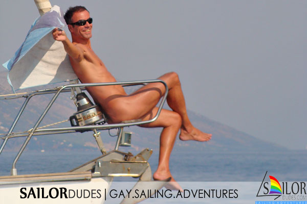 Nude guy sitting on sailing yacht bow in Greece