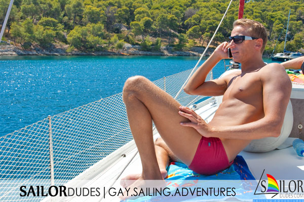 Smiling gay guy on sailing yacht
