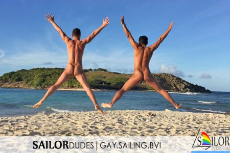 Two nude gay guys jumping on beach in BVI