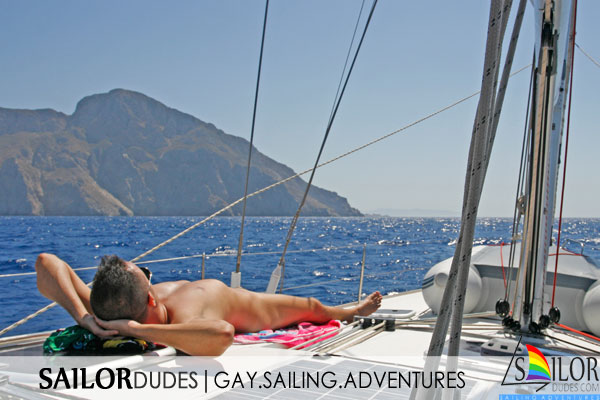 Nude gay guy lying on back on sailing yacht deck