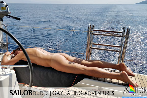Naked gay guy sunbathing on sailing yacht