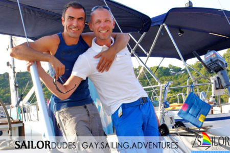 Two gay skippers on stern of sailing yacht