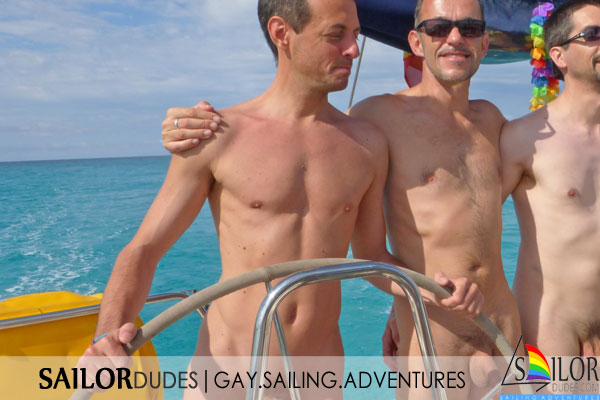 Nude gay guys behind sailing yacht steering wheel in Greece