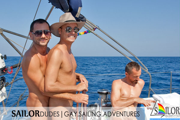Two naked gay guys steering sailing yacht