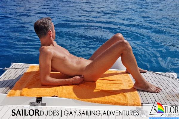 Nude skipper on sailing yacht swim deck